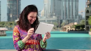 Woman stands near blue pool and skyscrapers and communicates via tablet pc. Businesswoman with tablet computer. Woman uses tablet pc. Female with white tablet PC with earphones talks through skype