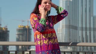 Woman stands near megatall skyscraper and speaks on smartphone. Businesswoman with mobile phone. Female with smartphone. Adult woman uses smartphone, Burj Khalifa in Dubai, United Arab Emirates