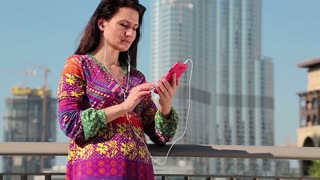 Woman stands near megatall skyscraper and uses smartphone. Female with smartphone. Businesswoman looks and flips through the photos in his smartphone. Adult woman uses smartphone