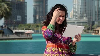 Woman stands near skyscraper and communicates via Tablet PC. Businesswoman with tablet computer. Adult woman uses tablet computer. Female with white tablet PC with earphones communicates through Skype