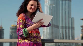 Woman stands near skyscraper and uses tablet computer. Attractive woman stands near skyscraper and makes photos on his Tablet PC. Female makes photos on his tablet pc. Adult woman uses tablet computer