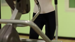 Woman trains in gym. The woman goes in for sports. Woman on a orbitrek exercise equipment. Physical activity helps burn up calories