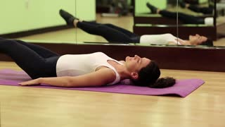 Woman trains in gym. Woman lies on the mat and pumps press. The woman goes in for sports. Physical activity helps burn up calories. Woman lying on the mat and pumps abdominal muscles