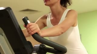 Woman trains in gym. Woman on exercise bicycle. Woman turns bicycle pedals. Woman sits on an exercise bike and turns pedals. The woman goes in for sports