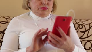 Woman uses red smartphone with earphones. Senior woman looking and flipping through the photos in her smartphone. Female with red smartphone