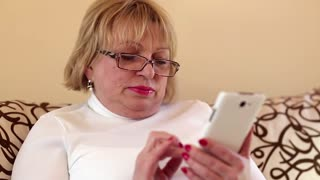 Woman uses white smartphone. Senior woman looks and flips through the photos in her smartphone. Female with smartphone