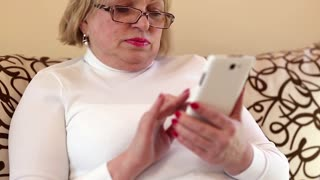 Woman using white smartphone. Senior woman looking and flipping through the photos in her smartphone