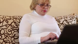 Woman with black laptop sits on the sofa. Blonde woman types text uses notebook. Female with notebook. Concentrated businesswoman with black laptop