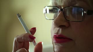 Woman with glasses smokes and watches TV. Woman with a cigarette. Female smoker, close up shot