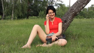 Woman with notebook and mobile phone on the nature
