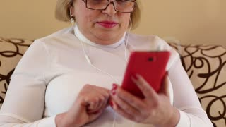 Woman with red smartphone sits on the sofa. Woman looks and flips through the photos in her smartphone