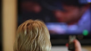 Woman with remote control switching tv channels. Back of the head