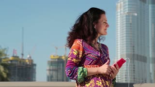 Woman with smartphone and earpieces listens to music and sings a song. Female with smartphone stands near megatall skyscraper. Adult woman near Burj Khalifa skyscraper in Dubai, United Arab Emirates