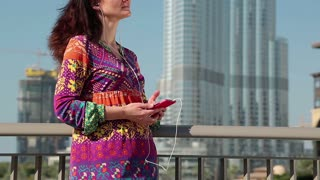 Woman with smartphone and earpieces listens to music. Female with smartphone stands near megatall skyscraper and listens to music. Woman near Burj Khalifa skyscraper in Dubai, United Arab Emirates