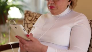 Woman with white smartphone speaks smiles, laughs and gesticulates. Woman talks on smartphone with webcam. Senior woman with cell phone talks sits on the divan. Female with smartphone