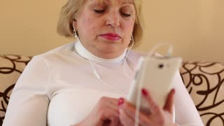 Woman with white smartphone speaks smiling, laughs and gesticulates. Woman talks on smartphone with webcam. Senior woman with cell phone talks sits on the sofa
