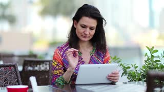 Woman with white tablet computer sits at a table in a cafe. Businesswoman with tablet computer. Female with tablet pc sits at a table in a coffee house. Adult woman uses tablet computer