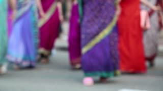 Women in Hindu traditional colorful costumes, dancing on the street, defocused video