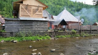 Wooden house near mountain river in Carpathians, Ukraine