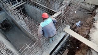 Worker at construction site. Unfinished construction. Building of foundation. Builder with red hard hat at project site