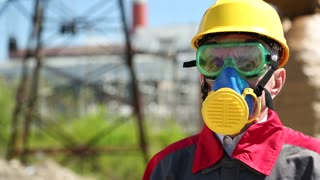 Worker in hard hat, goggles and respirator at heat electric power station