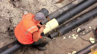 Worker in pipeline trench reconstruct hot water supply system by new technology
