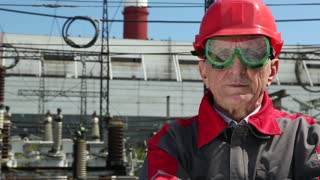 Worker in red hard hat at atomic power plant looking at the camera. Power engineering specialist at nuclear power plant