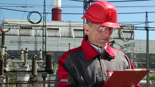 Worker in red hard hat at heat electric power station. Engineering supervision. The man writes in a worksheet. Supervisor at heat electric power station