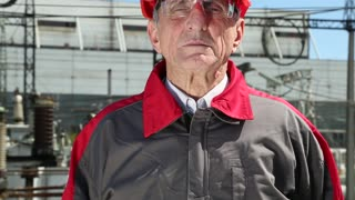 Worker in red hard hat at nuclear power plant looking at the camera. Power engineering specialist at atomic power station
