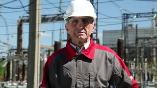 Worker in white hard hat at atomic power plant looking at the camera. Electrical fitter at nuclear power plant