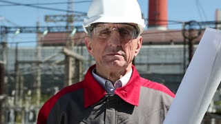 Worker in white hard hat at atomic power plant looks at the camera. Electrician at nuclear power plant. Powerman in white hard hat, protective goggles and drawings. Power engineer looks at the camera