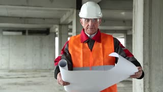 Worker in white hard hat with building drawings at project site. Manager of the works at construction site