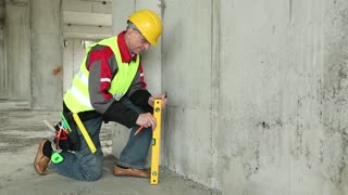 Worker in yellow hard hat with level at building site. Builder in yellow hard hat with level at project site