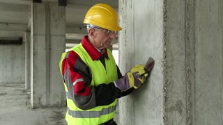 Worker with putty knife at construction site. Worker in yellow hard hat with putty knife at project site