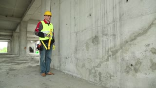 Worker with yellow level at building site. Worker in yellow hard hat with yellow level at project site