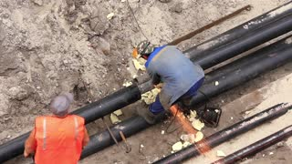 Workers in pipeline trench reconstruct hot water supply system by new technology