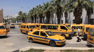 Yellow minibus and taxi on bus station in Sousse, Tunisia