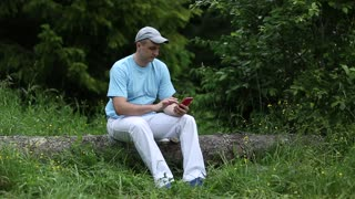 Young man in blue T-shirt sits on log, holds telephone, smiling. Weather is quiet. Summer sunny and warm day in the forest. Adjusted cap