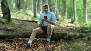Young man in blue T-shirt sits on log, talks on skype, showing surround nature. Says Hello and waving hand. Summer sunny and warm day in forest