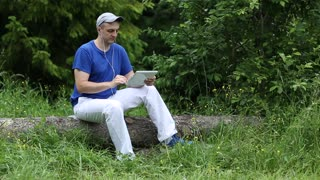 Young man in blue T-shirt with earpieces sits on log, holds keypad, touching screen, smiling. Weather is quiet. Summer sunny and warm day in the forest
