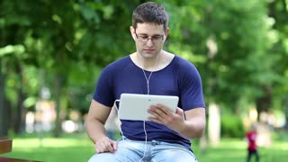 Young man sits on the bench in city park and communicates via tablet computer. Man in blue t-shirt sits on bench in public garden and speaks on tablet pc. Man with tablet pc communicates through skype