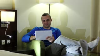 Young man with tablet pc with earpieces sits in chair. Man sits in armchair in hotel room and uses tablet computer