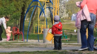 Youngster with yellow bucket on childrens playground