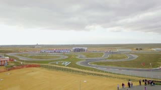 AERIAL VIEW. Full frame shot over territory of Russian karting championship with moving carts and spectators which took place in 2015 on the route in Yevpatoriya, Crimea