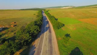 AERIAL VIEW. Several cars driving in both directions along track with green trees by sides situated between farm fields. Downwards shot