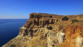 AERIAL VIEW. This is a picturesque moving video shot over hills and cliffs with several people on peak at magic bay with dark blue waters made at cape Fiolent, Sevastopol, Crimea. Majestic marine