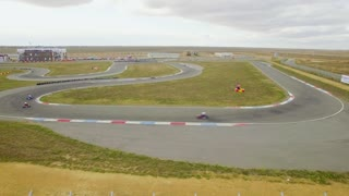 AERIAL VIEW. This is a sideward shot demonstrating karts racing each other along the serpentine track at the area of Russian karting championship which took place in 2015 on the route in Yevpatoriya