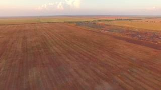 Camera is moving above agricultural fields showing aerial view of parts of land of different colors and some place looking like hilly terrain with some cars standing nearby
