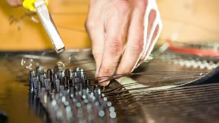 Close-up footage of disassembly of old piano strings one by one