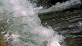 Close-up footage with audio of mad river torrent flowing, making a wave. Sound Included. Close-up